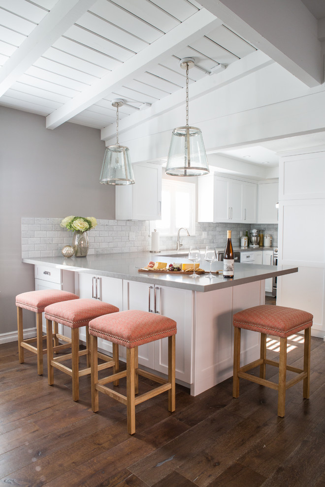 Example of a mid-sized transitional u-shaped medium tone wood floor eat-in kitchen design in Los Angeles with shaker cabinets, white cabinets, gray backsplash, a peninsula, stone tile backsplash and stainless steel appliances