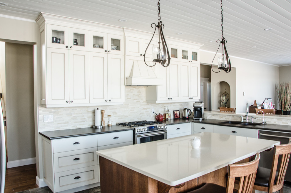 Example of a large transitional u-shaped medium tone wood floor eat-in kitchen design in Edmonton with a drop-in sink, shaker cabinets, white cabinets, laminate countertops, white backsplash, stone tile backsplash and stainless steel appliances