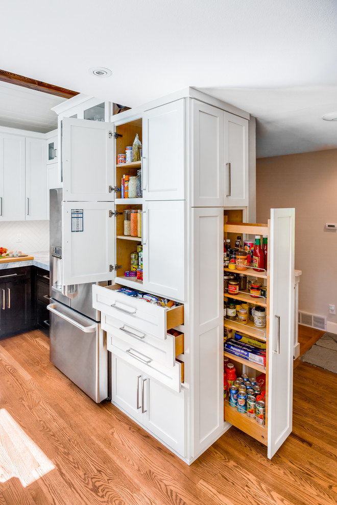 Transitional medium tone wood floor kitchen photo in Seattle with shaker cabinets, white cabinets and stainless steel appliances