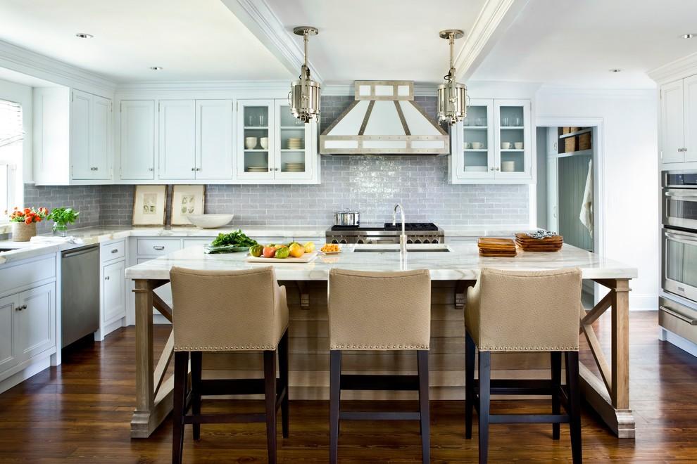 Kitchen - large coastal u-shaped medium tone wood floor kitchen idea in Jacksonville with an undermount sink, recessed-panel cabinets, white cabinets, gray backsplash, subway tile backsplash, stainless steel appliances and an island
