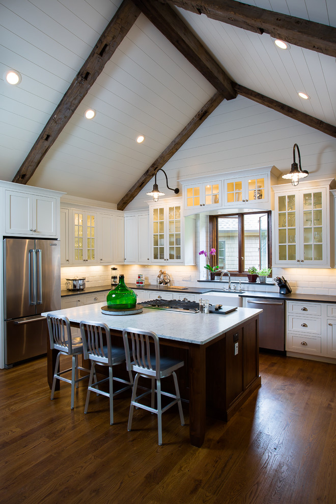 Inspiration for a mid-sized cottage l-shaped dark wood floor and brown floor open concept kitchen remodel in Atlanta with glass-front cabinets, white cabinets, stainless steel appliances, white backsplash, subway tile backsplash, an island, a farmhouse sink and marble countertops