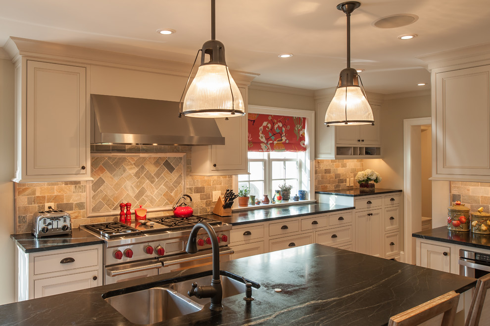 Example of a classic l-shaped enclosed kitchen design in Philadelphia with a double-bowl sink, beaded inset cabinets, white cabinets, multicolored backsplash, stainless steel appliances, travertine backsplash and soapstone countertops