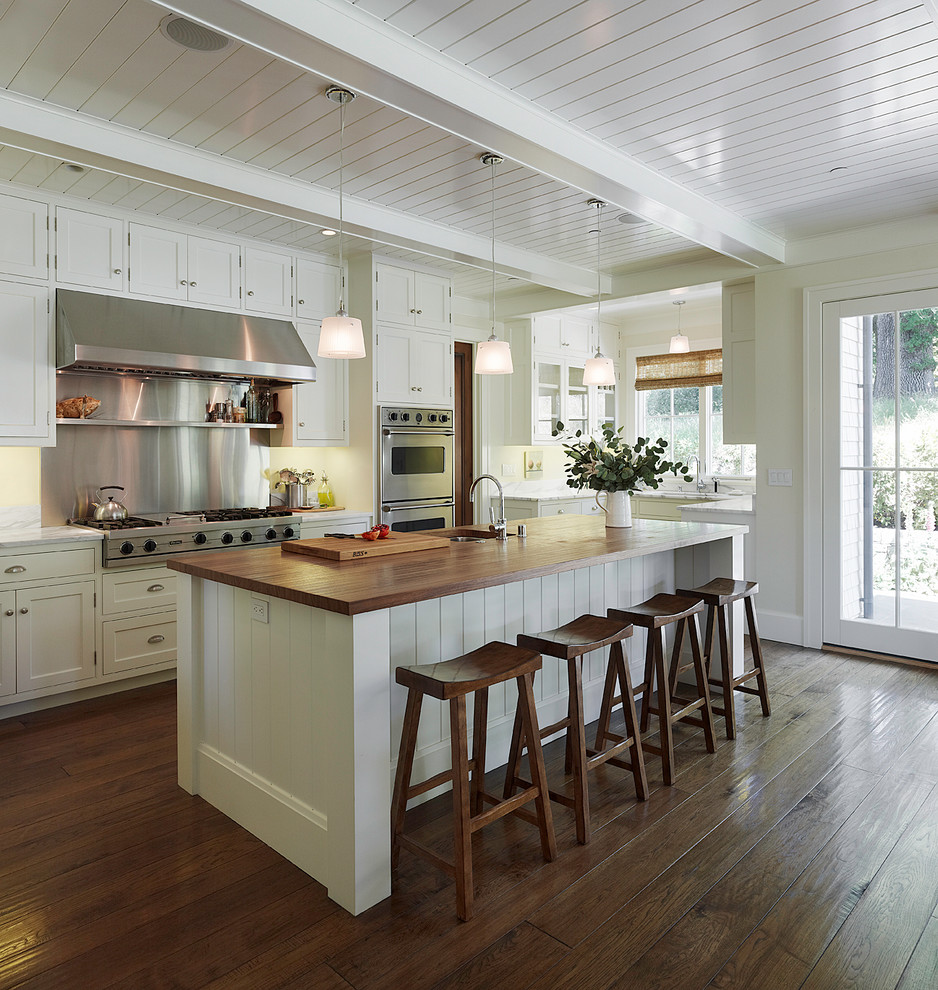 Elegant u-shaped dark wood floor open concept kitchen photo in San Francisco with stainless steel appliances, wood countertops, white cabinets, shaker cabinets, metallic backsplash, metal backsplash, an undermount sink and an island