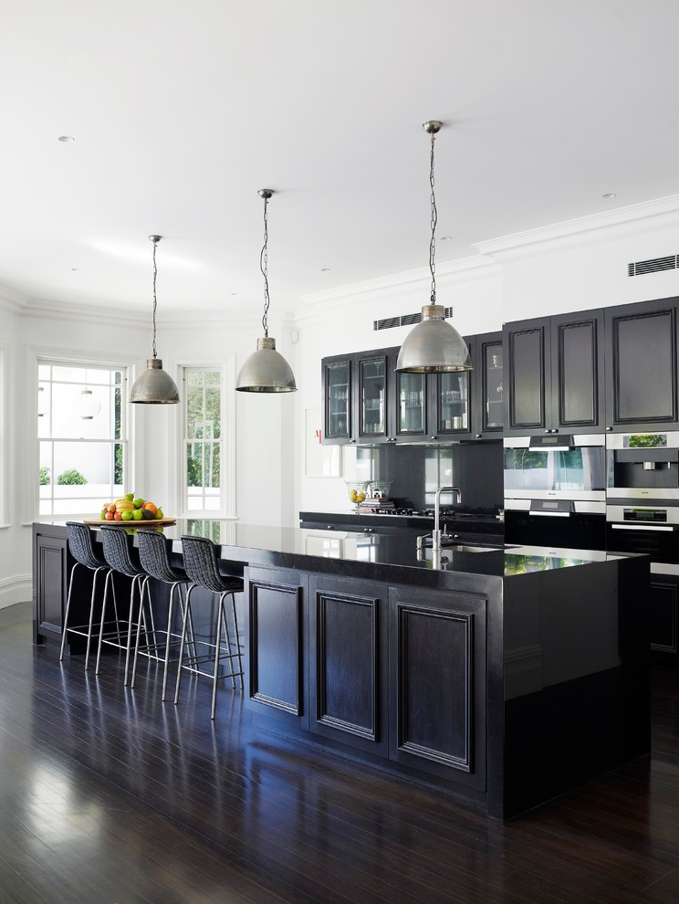 Inspiration for a timeless galley dark wood floor kitchen remodel in Sydney with recessed-panel cabinets, dark wood cabinets, stainless steel appliances and an island