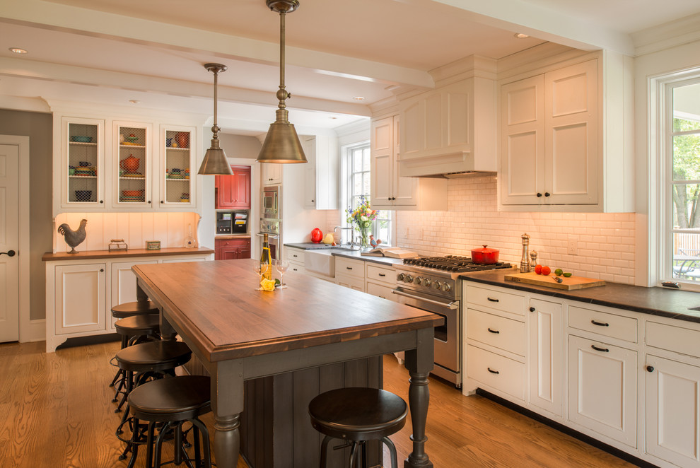 Eat-in kitchen - large traditional l-shaped medium tone wood floor eat-in kitchen idea in Philadelphia with a farmhouse sink, white cabinets, wood countertops, white backsplash, subway tile backsplash, beaded inset cabinets, stainless steel appliances and an island
