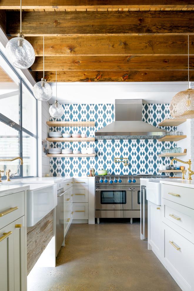 Landhausstil Küche in L-Form mit Landhausspüle, Schrankfronten im Shaker-Stil, weißen Schränken, bunter Rückwand, Rückwand aus Zementfliesen, Küchengeräten aus Edelstahl, Betonboden, Kücheninsel und grauem Boden in Austin