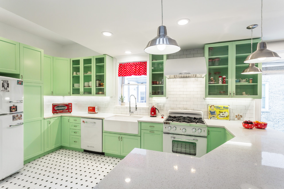Kitchen - mid-sized traditional multicolored floor kitchen idea in Chicago with a farmhouse sink, green cabinets, quartz countertops, white backsplash, subway tile backsplash, white appliances, a peninsula and glass-front cabinets