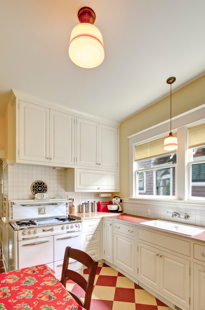 Example of a classic multicolored floor eat-in kitchen design in Portland with a drop-in sink, white appliances, laminate countertops, white cabinets, white backsplash, raised-panel cabinets and red countertops
