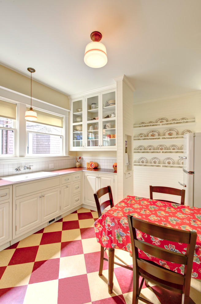 Example of a classic kitchen design in Portland with a drop-in sink, glass-front cabinets, white cabinets, laminate countertops and white appliances