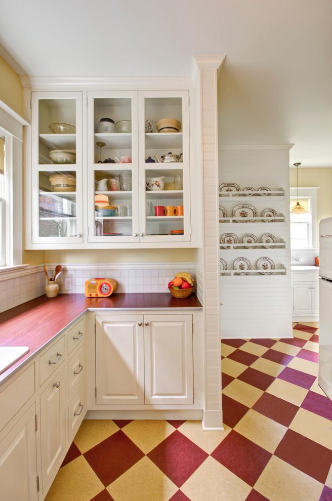 Elegant multicolored floor kitchen photo in Portland with raised-panel cabinets, white cabinets, laminate countertops, white backsplash and white appliances