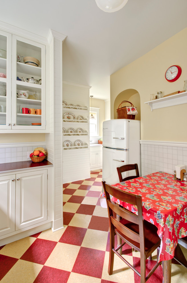 Eat-in kitchen - traditional multicolored floor eat-in kitchen idea in Portland with raised-panel cabinets, white cabinets, laminate countertops, white backsplash, white appliances and red countertops