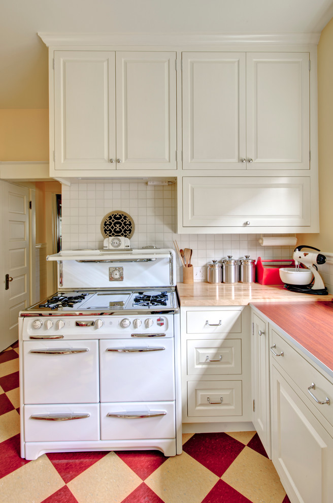 Country kitchen photo in Portland with raised-panel cabinets, white cabinets, laminate countertops, white backsplash and white appliances