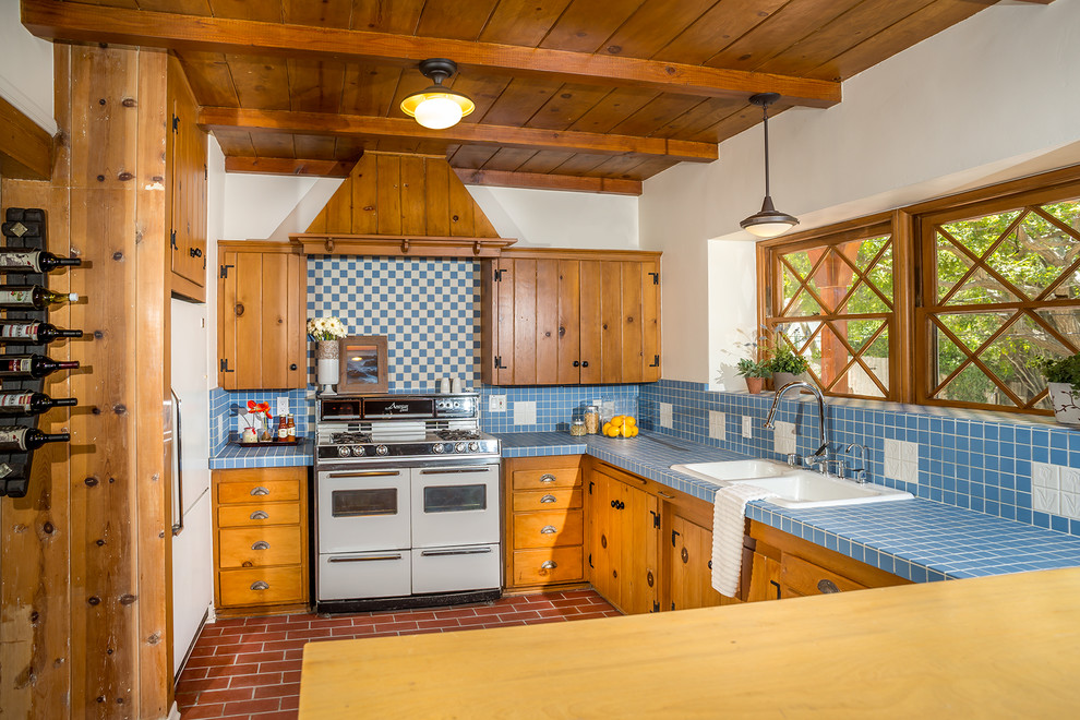 Mid-sized elegant l-shaped brick floor kitchen photo in Los Angeles with a drop-in sink, medium tone wood cabinets, tile countertops, white appliances, shaker cabinets, blue backsplash, porcelain backsplash and blue countertops
