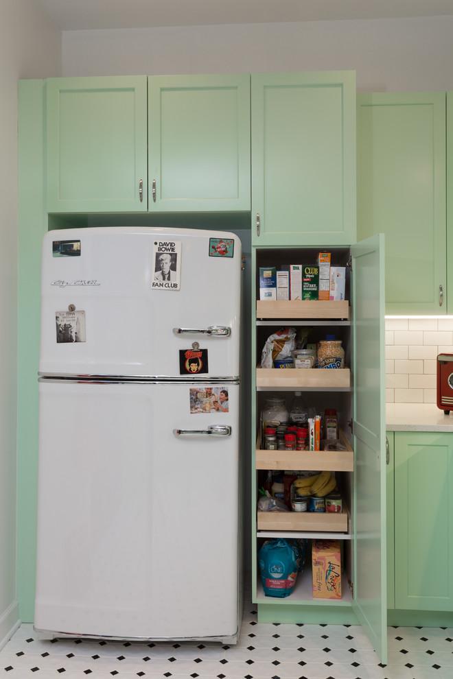 Mid-sized elegant l-shaped porcelain tile open concept kitchen photo in Chicago with a farmhouse sink, shaker cabinets, green cabinets, quartz countertops, white backsplash, subway tile backsplash, white appliances and a peninsula