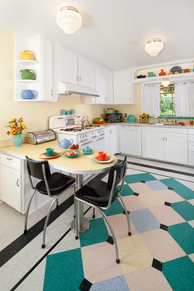 Inspiration for a mid-sized mid-century modern u-shaped linoleum floor and multicolored floor kitchen remodel in Santa Barbara with white cabinets, laminate countertops, white appliances, shaker cabinets, a double-bowl sink, an island and white countertops