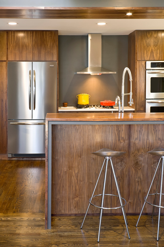 Mid-sized trendy u-shaped kitchen photo in Kansas City with flat-panel cabinets, medium tone wood cabinets, wood countertops and stainless steel appliances