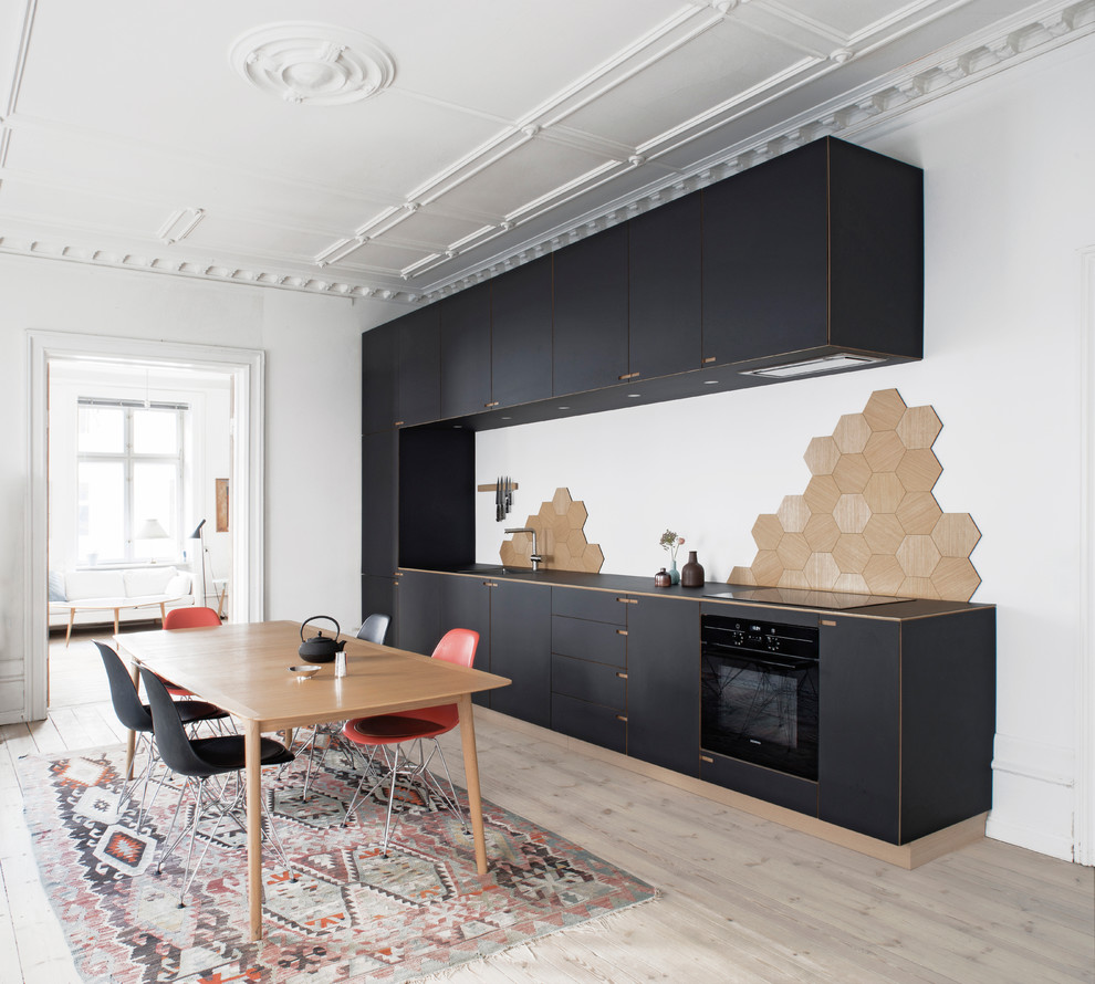 Eat-in kitchen - large scandinavian single-wall light wood floor eat-in kitchen idea in Copenhagen with flat-panel cabinets, black cabinets, beige backsplash, black appliances, no island, a drop-in sink and wood countertops