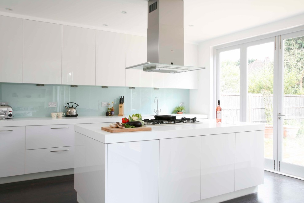 Example of a large minimalist galley dark wood floor kitchen design in London with flat-panel cabinets, white cabinets, solid surface countertops, white backsplash, glass sheet backsplash, stainless steel appliances and an island