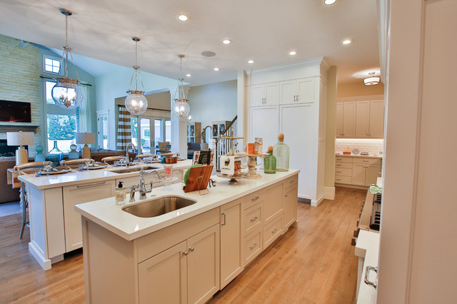 Large transitional galley light wood floor open concept kitchen photo in Salt Lake City with an undermount sink, shaker cabinets, white cabinets, quartzite countertops, white backsplash, subway tile backsplash, stainless steel appliances and two islands