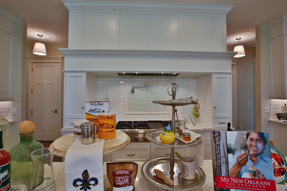 Large transitional u-shaped light wood floor open concept kitchen photo in Salt Lake City with shaker cabinets, white cabinets, white backsplash, stainless steel appliances, two islands, an undermount sink, quartzite countertops and subway tile backsplash