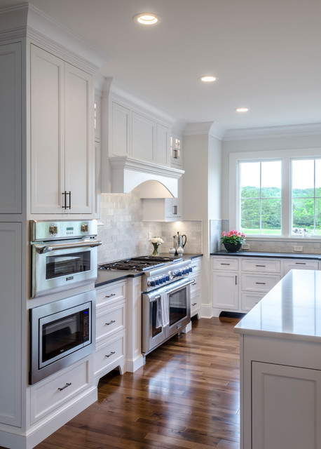 Example of a large classic medium tone wood floor and brown floor kitchen design in Cleveland with shaker cabinets, gray backsplash, subway tile backsplash, stainless steel appliances, an island, an undermount sink and white cabinets