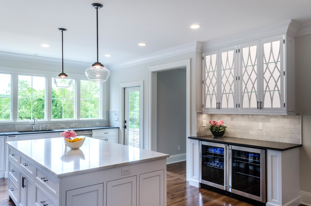 Kitchen - transitional medium tone wood floor and brown floor kitchen idea in Cleveland with shaker cabinets, gray backsplash, subway tile backsplash, stainless steel appliances and an island