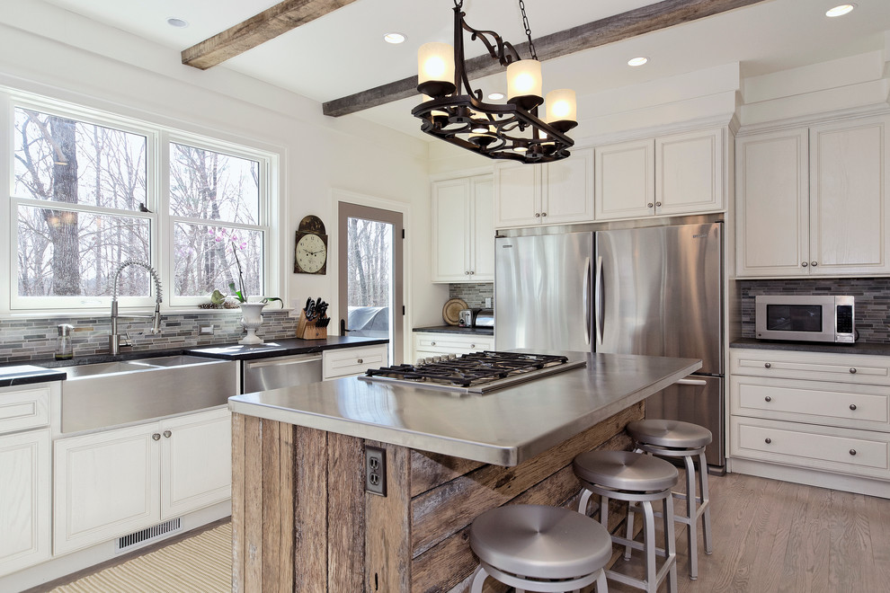Kitchen - transitional u-shaped kitchen idea in Other with a farmhouse sink, raised-panel cabinets, white cabinets, gray backsplash, matchstick tile backsplash, stainless steel appliances and zinc countertops