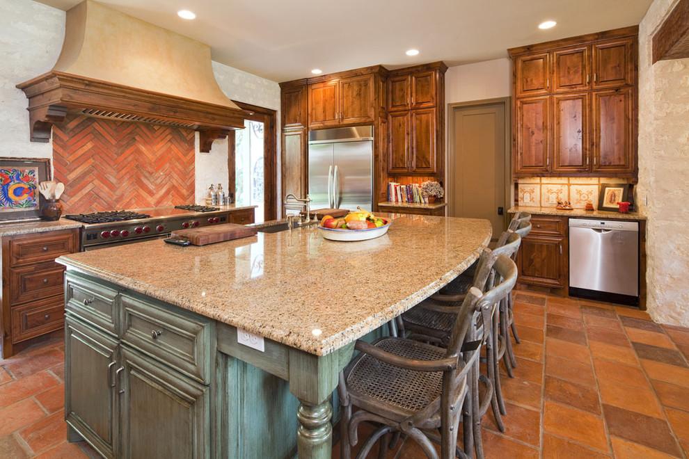 Kitchen - mediterranean kitchen idea in Austin with stainless steel appliances, raised-panel cabinets, dark wood cabinets and red backsplash