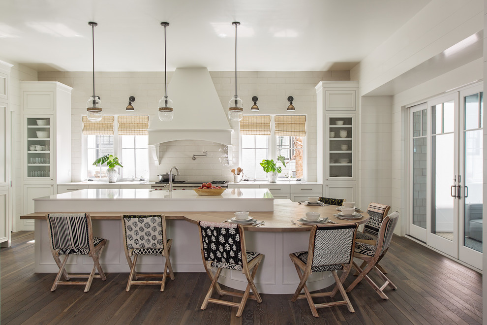 Example of a beach style l-shaped dark wood floor and brown floor eat-in kitchen design in Charleston with recessed-panel cabinets, white cabinets, white backsplash, stainless steel appliances, an island and white countertops