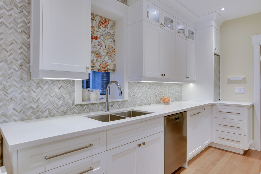 Inspiration for a mid-sized transitional galley medium tone wood floor kitchen remodel in Toronto with an undermount sink, shaker cabinets, white cabinets, quartz countertops, gray backsplash, stone tile backsplash, stainless steel appliances and no island
