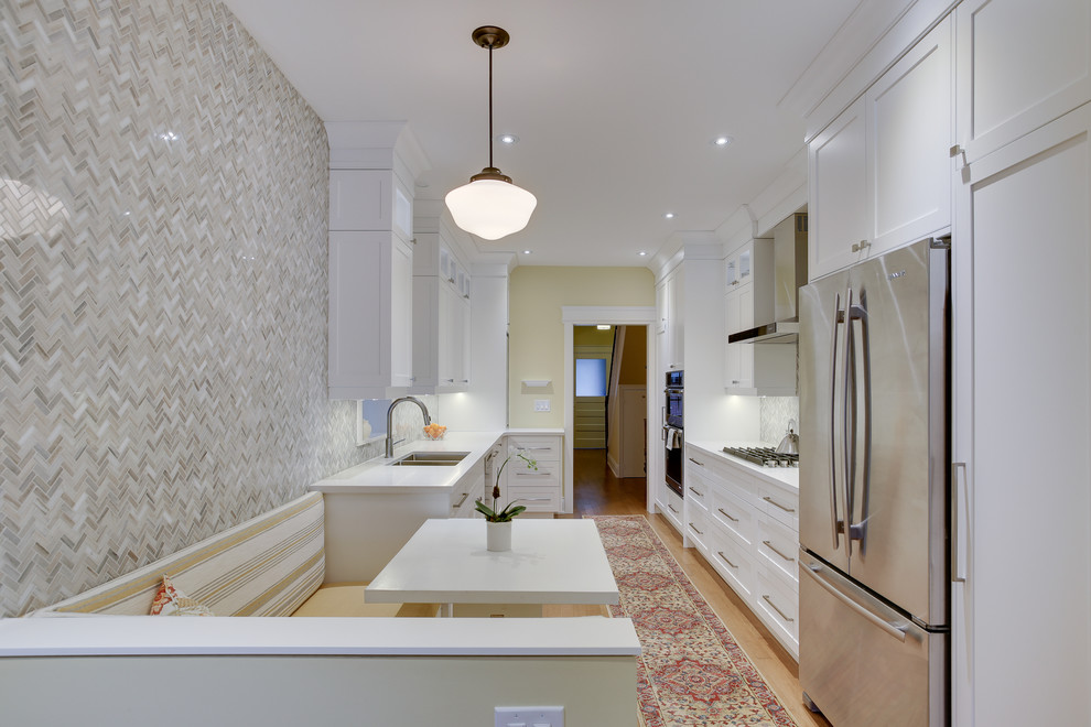 Example of a mid-sized classic galley medium tone wood floor kitchen design in Toronto with an undermount sink, shaker cabinets, white cabinets, quartz countertops, gray backsplash, stone tile backsplash, stainless steel appliances and no island