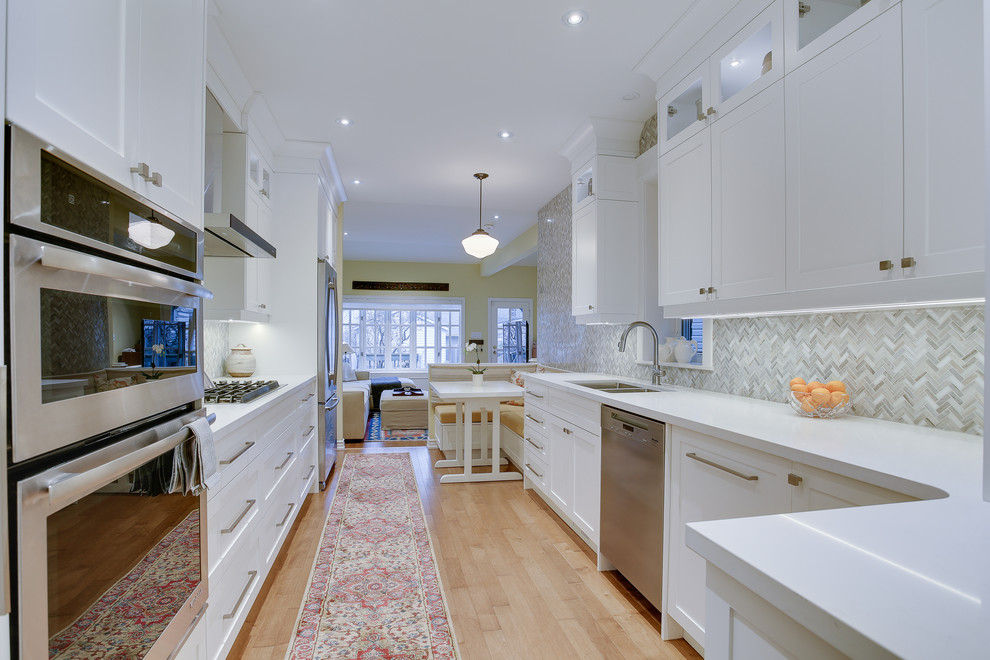 Example of a mid-sized transitional galley medium tone wood floor kitchen design in Toronto with an undermount sink, shaker cabinets, white cabinets, quartz countertops, gray backsplash, stone tile backsplash, stainless steel appliances and no island