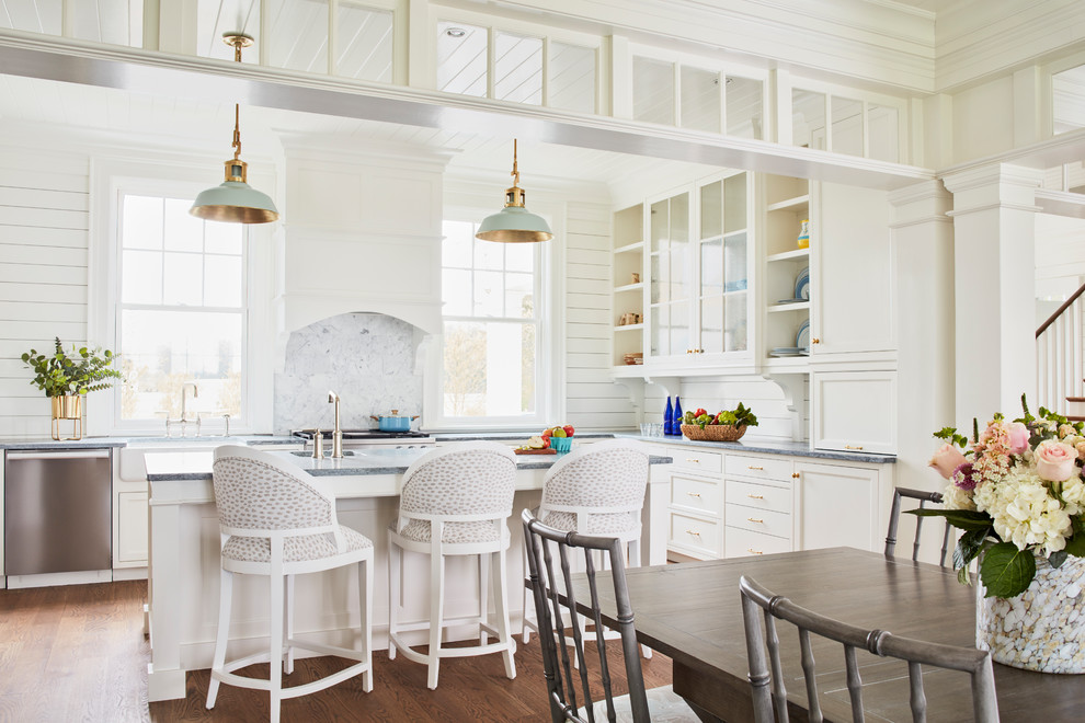 Eat-in kitchen - cottage u-shaped medium tone wood floor and brown floor eat-in kitchen idea in Richmond with a farmhouse sink, recessed-panel cabinets, white cabinets, soapstone countertops, white backsplash, marble backsplash, stainless steel appliances, an island and gray countertops