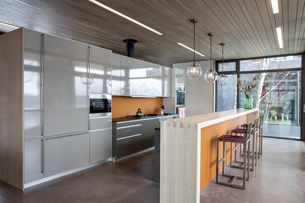 Inspiration for a contemporary galley kitchen remodel in New York with flat-panel cabinets, gray cabinets, orange backsplash and paneled appliances