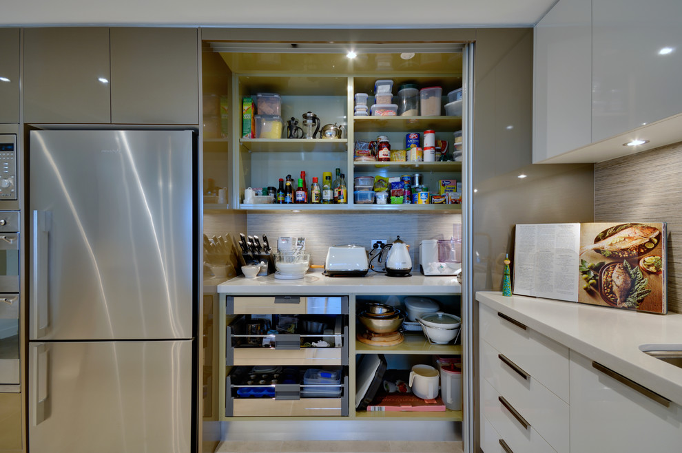 Example of a trendy kitchen design in Brisbane with flat-panel cabinets, white cabinets and stainless steel appliances