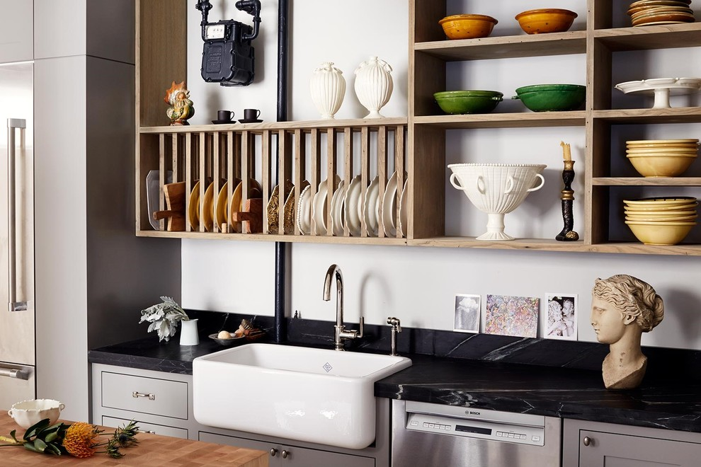Example of a mid-sized transitional l-shaped concrete floor enclosed kitchen design in New York with a farmhouse sink, shaker cabinets, gray cabinets, soapstone countertops, black backsplash, stone slab backsplash, stainless steel appliances and an island
