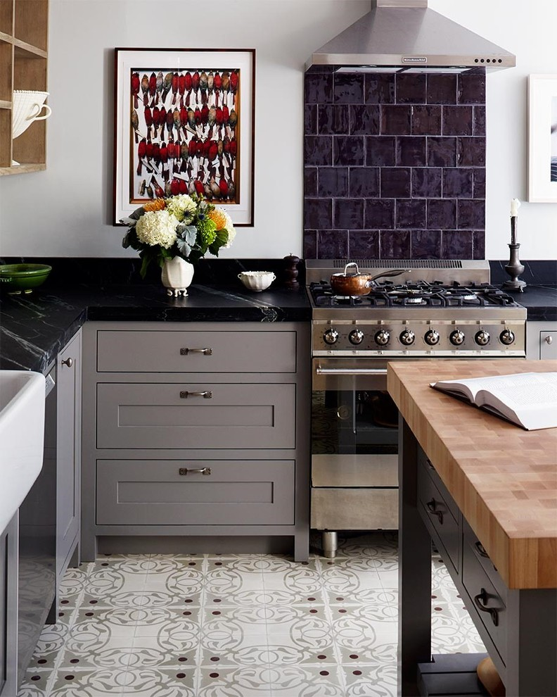 Enclosed kitchen - mid-sized transitional l-shaped enclosed kitchen idea in New York with a farmhouse sink, shaker cabinets, gray cabinets, soapstone countertops, black backsplash, stainless steel appliances, an island and stone tile backsplash