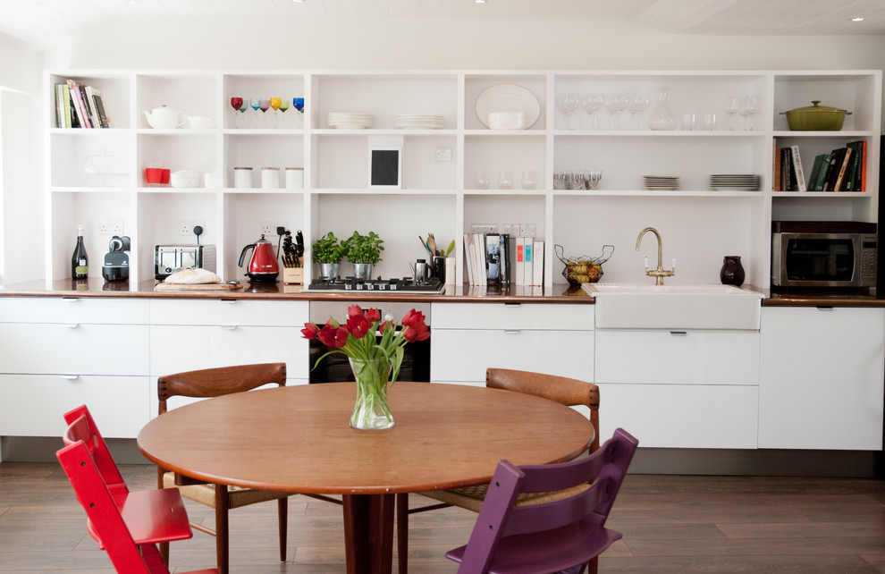 Trendy galley medium tone wood floor eat-in kitchen photo in London with a farmhouse sink, open cabinets and white cabinets