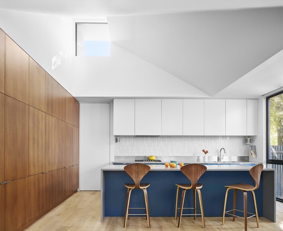 Photo of a contemporary kitchen in Austin with an island, flat-panel cabinets, white cabinets, white splashback, light hardwood floors and grey benchtop.