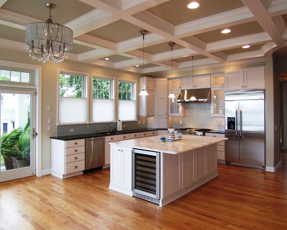 Mid-sized elegant l-shaped medium tone wood floor open concept kitchen photo in Baltimore with stainless steel appliances, white cabinets, mosaic tile backsplash, shaker cabinets, quartz countertops, an undermount sink, white backsplash and an island