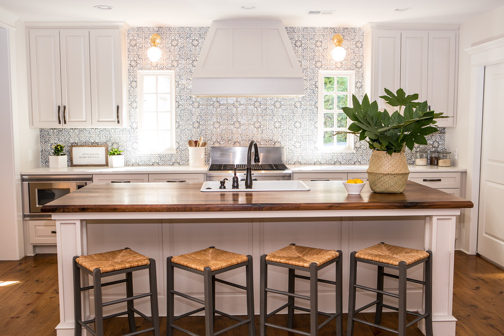 Mid-sized country galley medium tone wood floor and brown floor eat-in kitchen photo in Atlanta with shaker cabinets, gray cabinets, quartz countertops, blue backsplash, terra-cotta backsplash, stainless steel appliances, an island and a drop-in sink