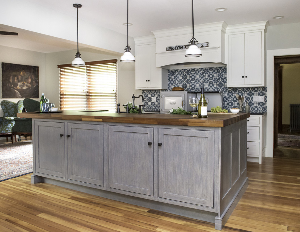 Mid-sized mountain style galley medium tone wood floor and brown floor open concept kitchen photo in Boston with a farmhouse sink, beaded inset cabinets, white cabinets, wood countertops, blue backsplash, cement tile backsplash, paneled appliances, an island and black countertops