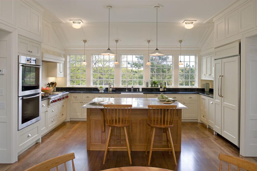 Ornate u-shaped kitchen photo in Boston with paneled appliances
