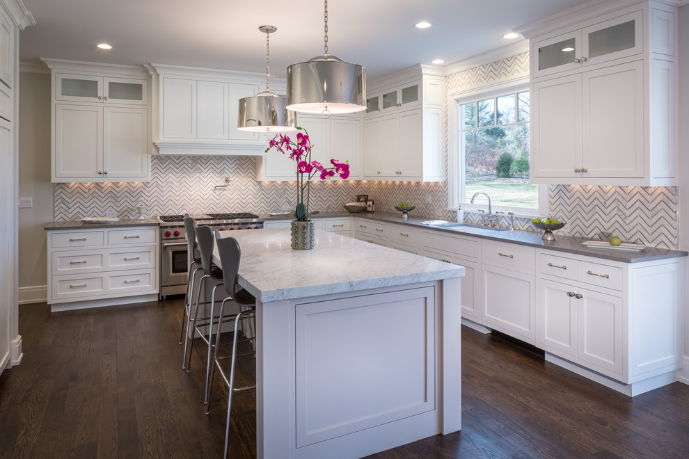 Transitional l-shaped dark wood floor kitchen photo in New York with an undermount sink, shaker cabinets, white cabinets, multicolored backsplash, stainless steel appliances, an island and gray countertops