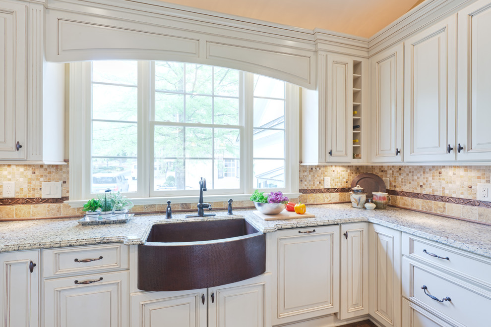 Inspiration for a large timeless u-shaped medium tone wood floor and brown floor eat-in kitchen remodel in Atlanta with raised-panel cabinets, a farmhouse sink, white cabinets, granite countertops, multicolored backsplash, travertine backsplash, stainless steel appliances, a peninsula and beige countertops