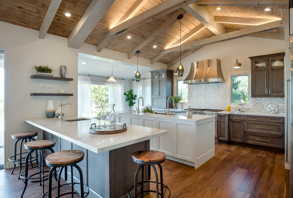 Large country galley medium tone wood floor and brown floor open concept kitchen photo in Los Angeles with quartz countertops, multicolored backsplash, stainless steel appliances, two islands, raised-panel cabinets, dark wood cabinets, cement tile backsplash, an undermount sink and white countertops
