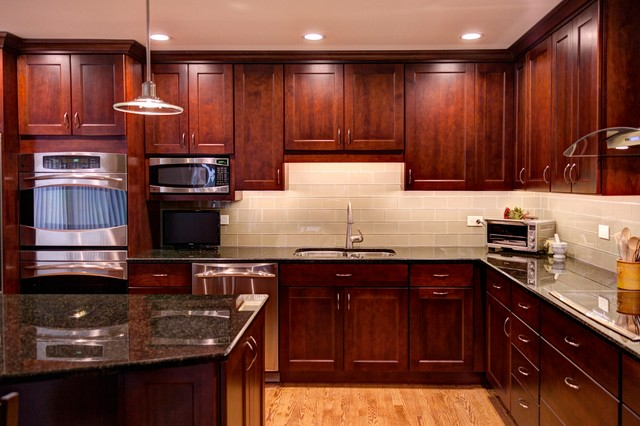 Example of a transitional l-shaped open concept kitchen design in Chicago with an undermount sink, flat-panel cabinets, dark wood cabinets, granite countertops, beige backsplash, glass tile backsplash and stainless steel appliances