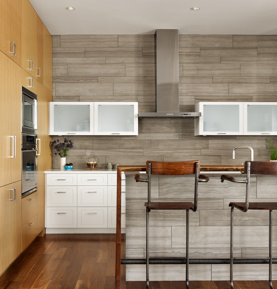 Inspiration for a contemporary galley kitchen remodel in Austin with flat-panel cabinets, white cabinets, gray backsplash and stainless steel appliances