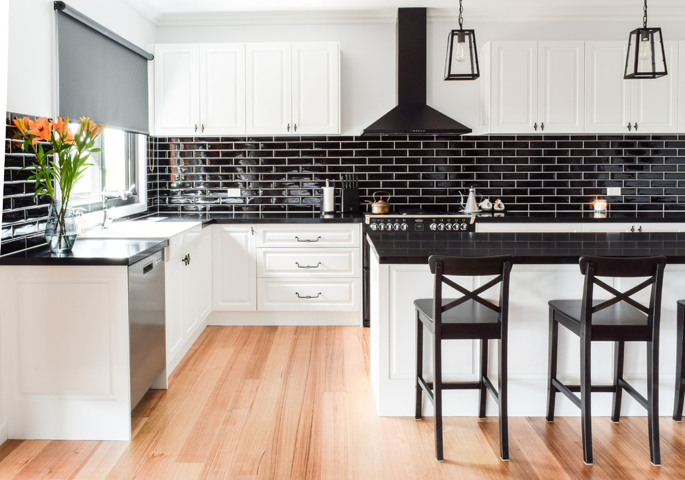 Example of a large transitional l-shaped brown floor and medium tone wood floor open concept kitchen design in Melbourne with a farmhouse sink, quartz countertops, black backsplash, subway tile backsplash, black appliances, an island and raised-panel cabinets