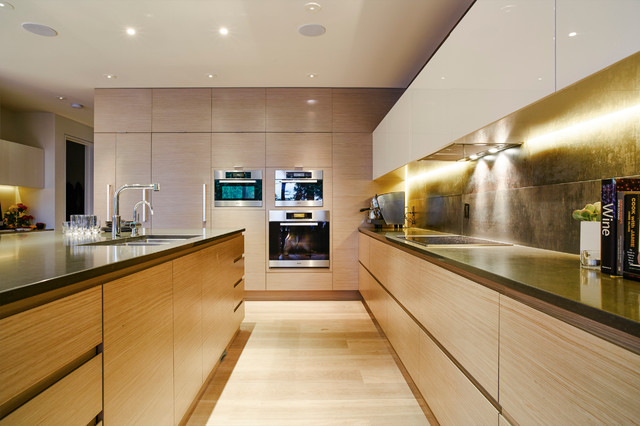 Large trendy l-shaped light wood floor eat-in kitchen photo in Vancouver with an undermount sink, flat-panel cabinets, light wood cabinets, quartz countertops, metallic backsplash, porcelain backsplash, stainless steel appliances and an island